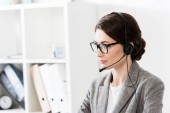 Photo attractive call center operator in glasses and headset looking away in office