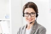 usmívající se krásné call centrum operátor v brýle a sluchátka, při pohledu na fotoaparát v úřadu