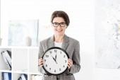 Fotografie portrét usmívající se atraktivní podnikatelka drží nástěnné hodiny a při pohledu na fotoaparát v úřadu