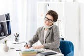 Fotografie s úsměvem atraktivní podnikatelka mluví stacionární telefonicky v kanceláři a při pohledu na fotoaparát