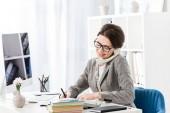 s úsměvem atraktivní podnikatelka mluví stacionární telefonicky v kanceláři
