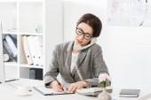 s úsměvem atraktivní podnikatelka v brýlích mluví stacionární telefonicky v kanceláři