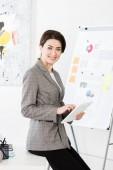 usmívající se atraktivní podnikatelka v šedém obleku sedí na stole a používání tabletu v kanceláři