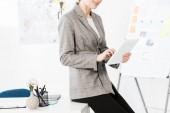 oříznutý obraz podnikatelka v šedém obleku sedí na stole a používání tabletu v kanceláři