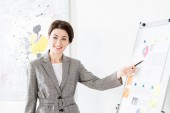 Fotografie smiling beautiful businesswoman in grey suit pointing on flipchart during project presentation in office