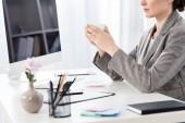 oříznutého obrazu podnikatelka v šedém obleku drží šálek kávy u stolu v kanceláři