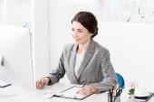 Fotografie Lächelnde attraktive Geschäftsfrau im grauen Anzug schreibt im Büro etwas ans Klemmbrett