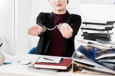 cropped image of businesswoman showing hands with handcuffs in office