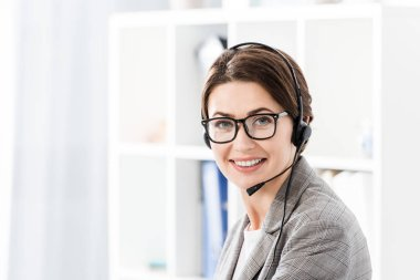 Smiling attractive call center operator in glasses and headset looking at camera in office stock vector