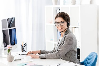 smiling attractive call center operator in glasses and headset using computer at table in office, looking at camera