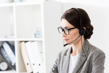 Attractive call center operator in glasses and headset looking away in office stock vector