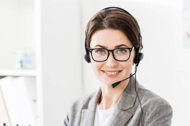 Smiling beautiful call center operator in glasses and headset looking at camera in office stock vector