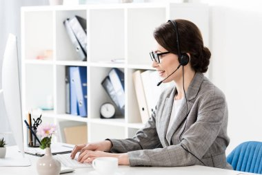 side view of smiling attractive call center operator in glasses and headset using computer at table in office