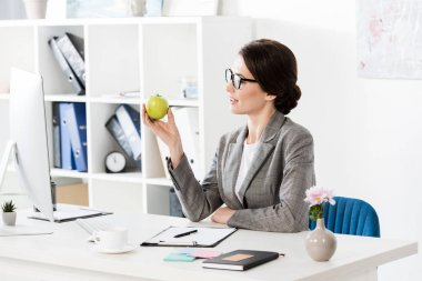 Attractive businesswoman looking at apple in office stock vector