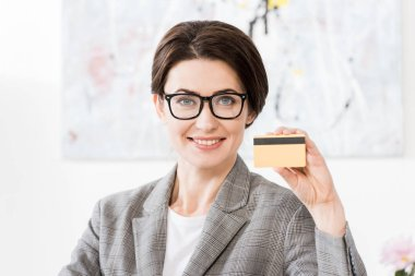 Attractive businesswoman in glasses showing credit card and looking at camera in office stock vector