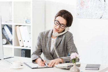 Smiling attractive businesswoman in glasses talking by stationary telephone in office stock vector