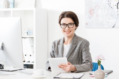 Smiling attractive businesswoman in grey suit using tablet and looking at camera in office stock vector