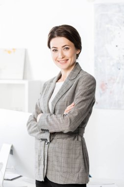 Smiling attractive businesswoman in grey suit standing with crossed arms and looking at camera in office stock vector