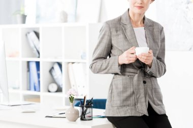 Cropped image of businesswoman in grey suit sitting on table and holding cup of coffee in office stock vector