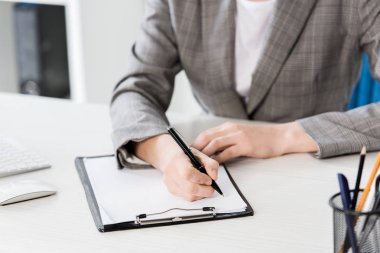 Cropped image of businesswoman in grey suit writing something to clipboard in office stock vector