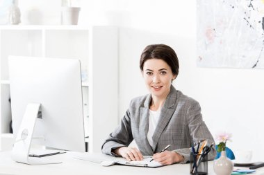 Attractive businesswoman in grey suit writing something to clipboard in office and looking at camera stock vector