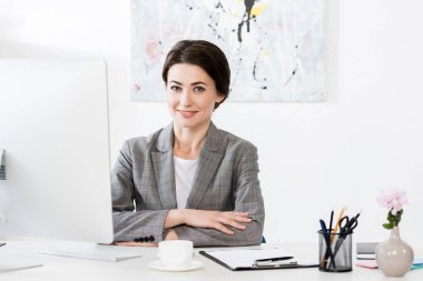 Attractive businesswoman in grey suit sitting at table with computer in office and looking at camera stock vector