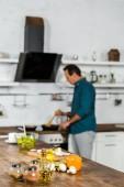 Fotografia messa a fuoco selettiva delluomo maturo, frittura di verdure in cucina, spezie sul ripiano del tavolo