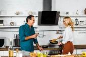Fotografie zralá žena, vaření na sporáku a manžel drží sklenku vína v kuchyni