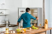 rear view of mature man looking into fridge in kitchen
