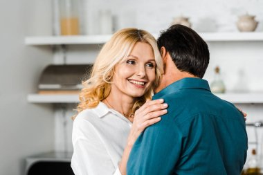 happy mature wife and husband cuddling in kitchen