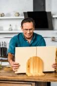 Fotografie usměvavý pohledný zralý muž vaření v kuchyni a pořizování kuchařka