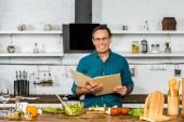 Krásný zralý muž vaření v kuchyni a držení kuchařka