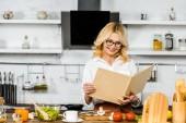 usmívající se atraktivní zralá žena čte kniha receptů pro vaření v kuchyni