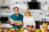 Fotografie pohled z vysokého úhlu zralé manželky a manžela vaření spolu s kuchařka v kuchyni
