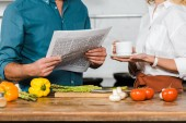 oříznutý obraz starší žena držící šálek čaje a manžel čtenářský deník při vaření v kuchyni