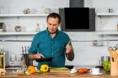 Fotografia uomo invecchiato centrale bello cucinare le verdure sulla vaschetta di frittura in cucina