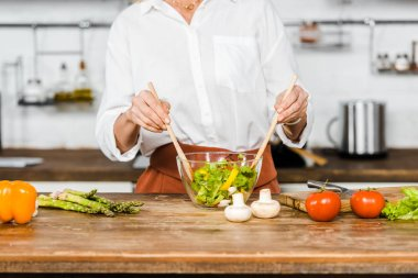 cropped image of mature woman mixing salad in glass bowl in kitchen