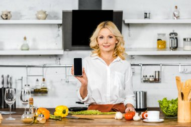 Attractive middle aged woman showing smartphone with blank screen in kitchen stock vector