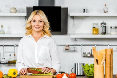 smiling beautiful middle aged woman cutting vegetables in kitchen and looking at camera