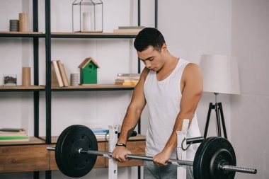 handsome  bi-racial man exercising in home gym
