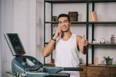 mosolyogva bi-faji sportember beszélt a smartphone és a hüvelykujj felbukkan