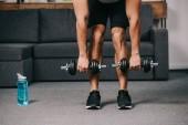 Fotografie verkürzten Blick auf starken muskulösen Mann Training mit Hanteln im Hause Fitness-Studio