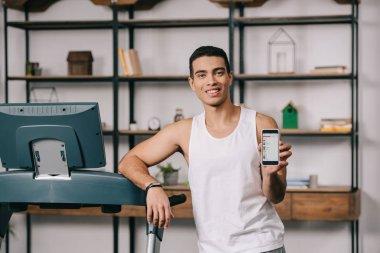 cheerful bi-racial man holding smartphone with apple music app on screen