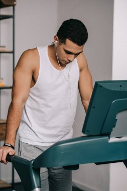 mixed race man exercising on treadmill and listening music in earphones