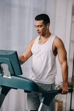 mixed race man listening music in earphones and exercising on treadmill