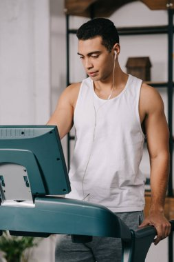 mixed race man listening music in earphones while exercising on treadmill