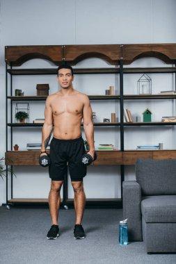 Muscular bi-racial man standing with heavy dumbbells in living room stock vector