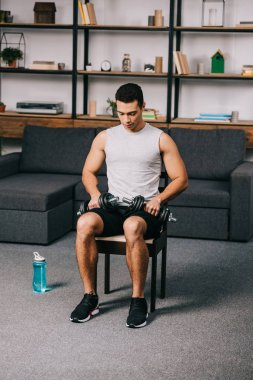 mixed race athlete sitting with dumbbells on chair in home gym