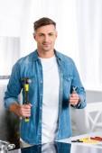 pohledný muž drží opravné nástroje a usmívá se na kameru