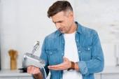 Fotografie Erwachsenen Mann halten Mixer in der hand und sah es verwirrt